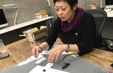 紙で作ったホールドリングのデザインコンセプトを説明する吉野