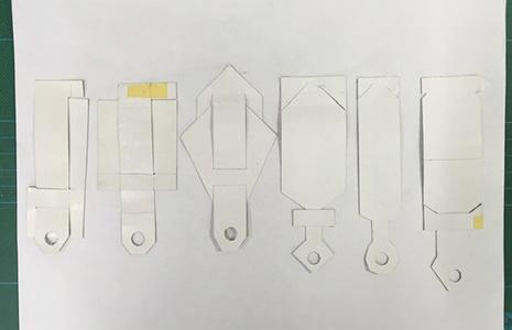携帯ストラップの紙サンプルを並べる
